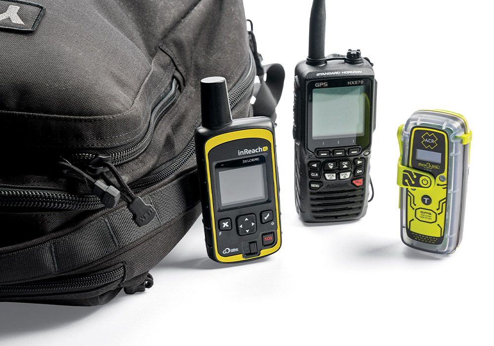 From left to right: A well-stocked, dedicated duffel or backpack designated as a ditch bag in case of emergency carries a satellite communicator/rescue beacon, a handheld VHF radio, and a personal locator beacon. Any one of them may be sufficient, but redundancy offers extra security.