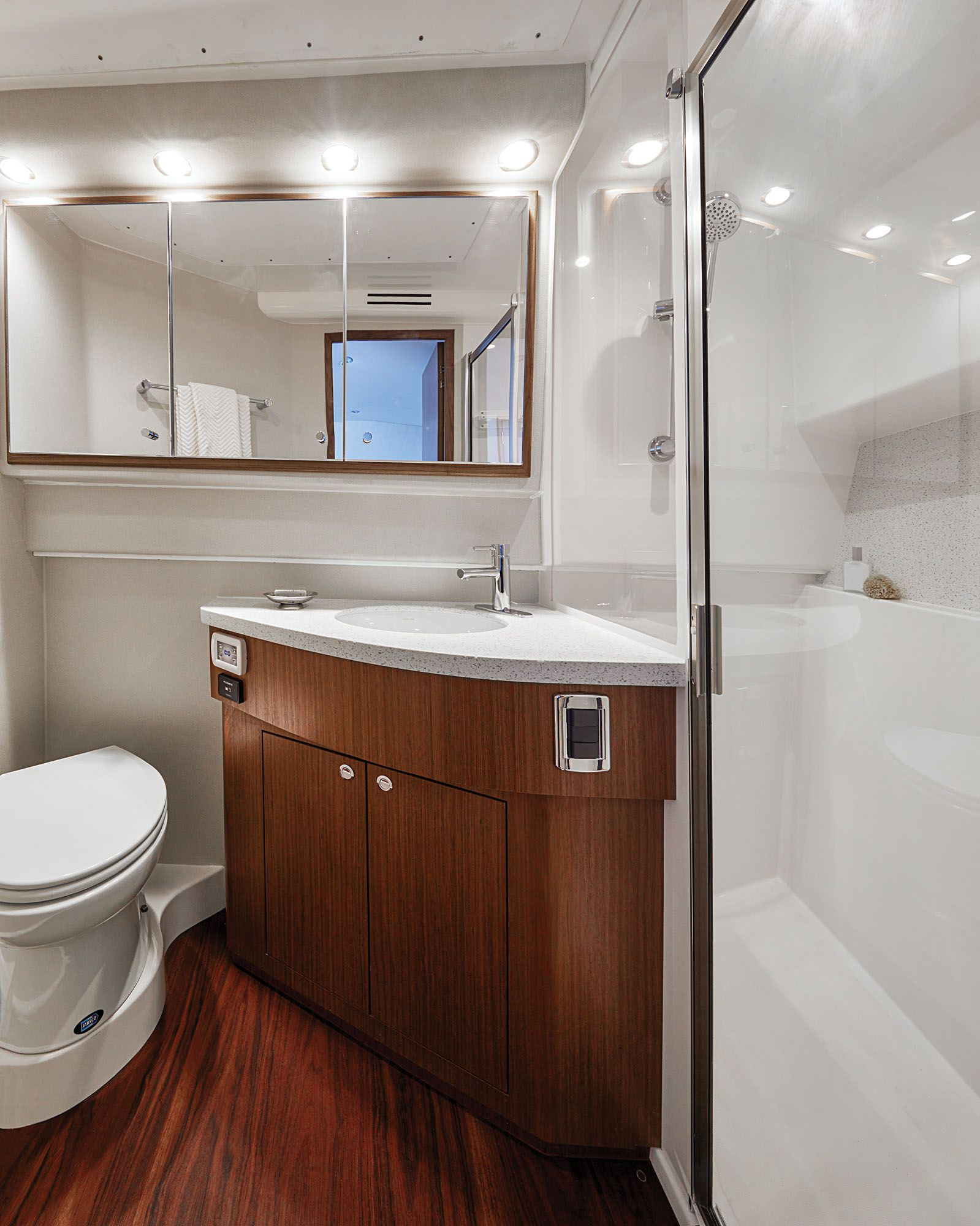 The head compartment offers an enclosed shower, a sink and vanity, and a flush toilet.