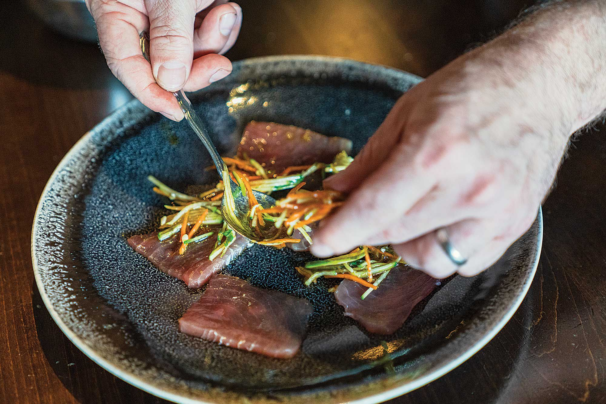 Plating and ­presentation is as easy as ­arranging the crudo and ­garnishing with the green papaya slaw.