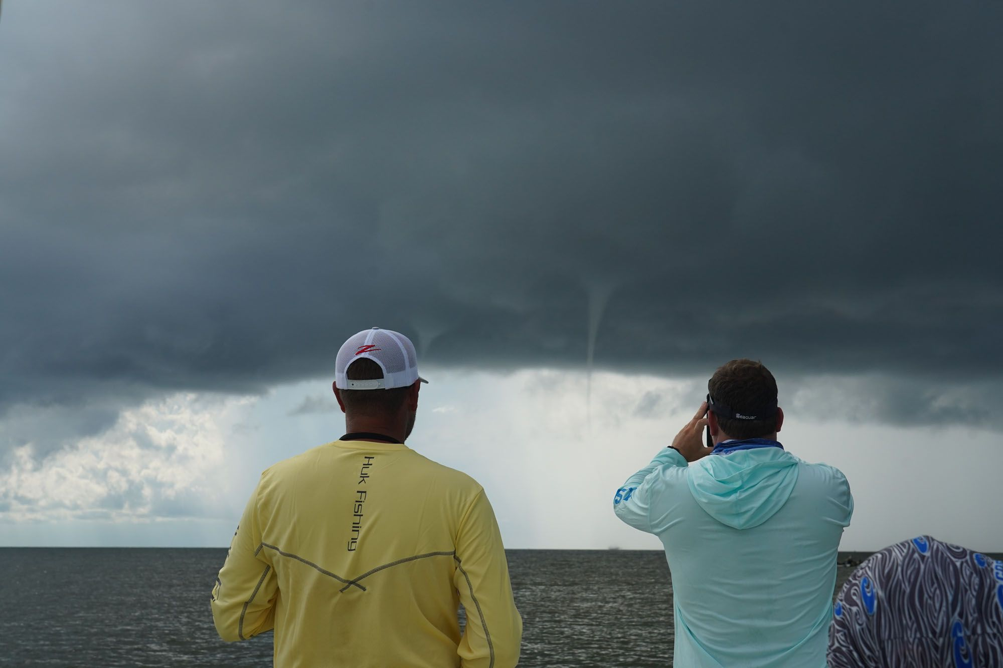 Time to move on. These waterspouts developed quickly. This one has already touched down; look closely at the horizon beneath the elbow of Brian Evans with Seaguar, and you can see the vortex whipping the water. As the black curtain descended, we hightailed it to the coast.